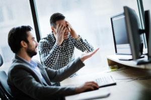 パソコンの前で頭を抱える男性たち