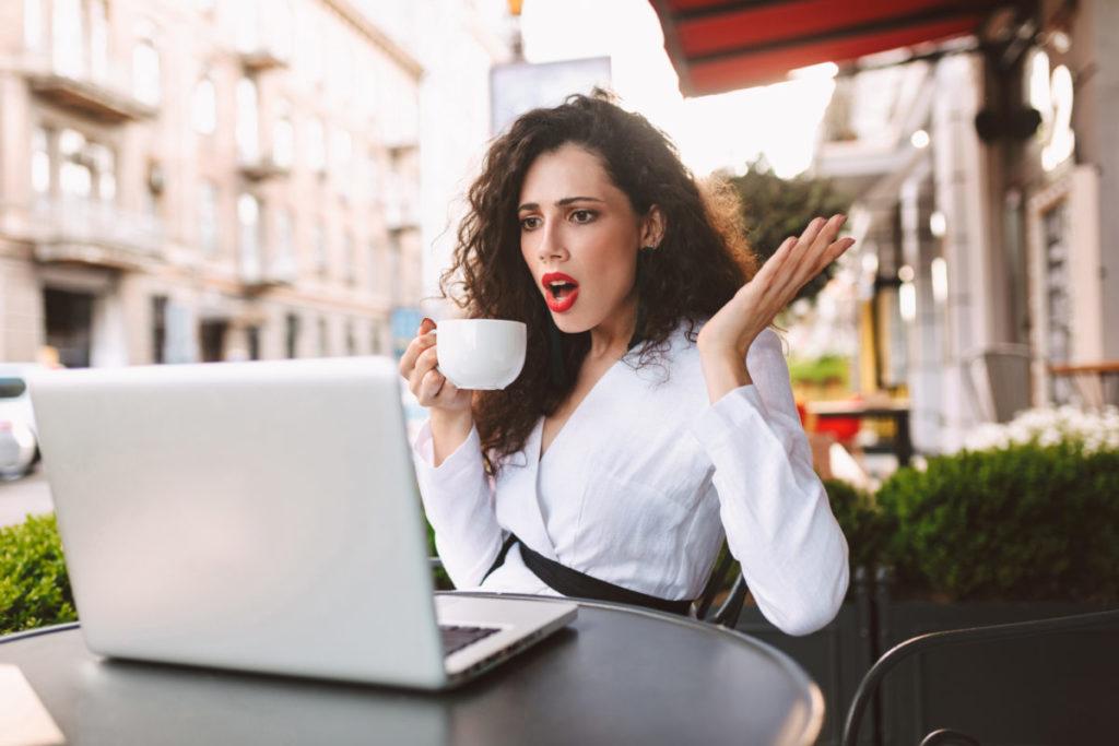 パソコンの前でショックを受ける女性