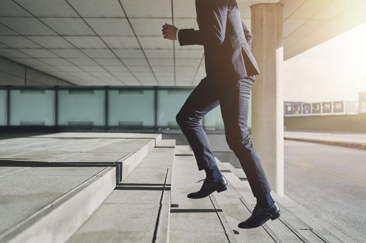 階段を上がるスーツの男性